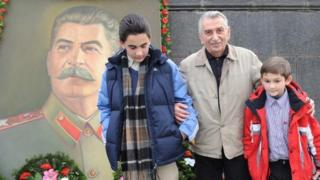 The grandson of Joseph Stalin, Yevgeny Dzhugashvili, (centre) poses with his grandsons next to a portrait of their famous relative in the central square of Gori, some 80km from Tbilisi (21 December 2009)