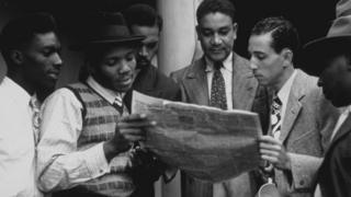 "Jamaicans reading a newspaper on board the ""Empire Windrush"""