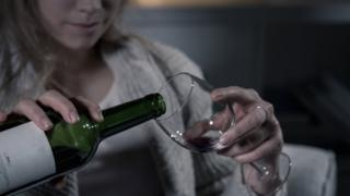 Woman pouring wine into glass