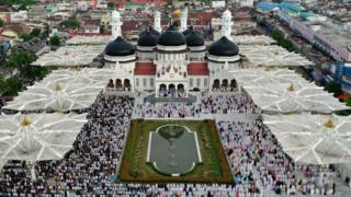 in_pictures An aerial photograph shows people attending Eid al-Fitr prayers at Baiturrahman Mosque in Banda Aceh, Indonesia