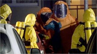 Firefighters wear protective suits during an investigation for poisonous substances at a house near the place where a courier driver was found dead inside his van in Haldensleben
