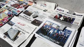 Iranian newspapers, bearing pictures related to the nuclear deal on their front pages, lay on the ground in front of a kiosk in Tehran on 4 April 2015