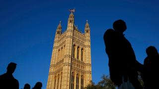 Silhouetted people walk past the Houses of Parliament