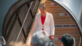 Theresa May getting off a plane