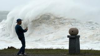 A young man takes pictures of high waves generated by typhoon Hagibis in Atawa, Mie Prefecture, Japan, 12 October 2019.