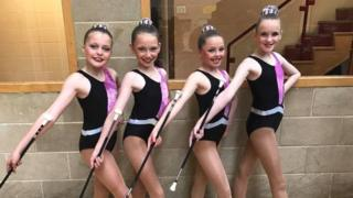 Four young twirlers in leotards