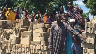 People looked on as Nigeria's richest man, the businessman Aliko Dangote, along with the Irish rock star Bono visited camps where some of the 2.5 million displaced by the fighting are now sheltering on 28 August 2016