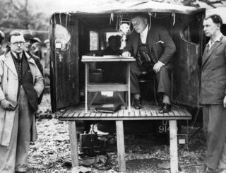 Picture shows outside broadcast van with microphones, equipment and reporters at Loch Lomond in 1932.