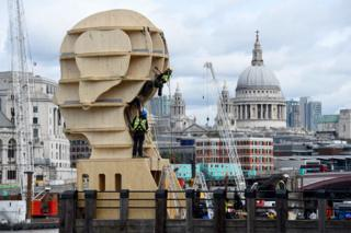 Workmen install a sculpture called Head Above Water in London