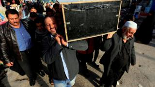 Iraqis carry the coffin of a victim during a funeral in the holy city of Najaf, Iraq, 15 January