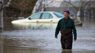 Jean-Jacques Seguin wades though flood water after he evacuated his house in Rigaud, Quebec