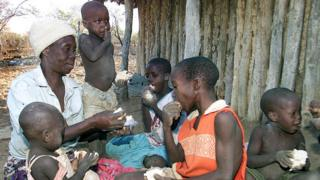 A Zimbabwean grandmother hands out bread to her family