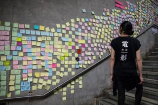 in_pictures A woman walks past a wall in Hong Kong covered with sticky note messages