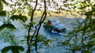 A 4x4 driving through the river Usk