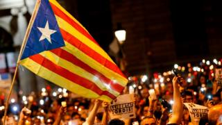 People hold candles during a demonstration in Barcelona against the arrest of two Catalan separatist leaders