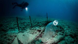 A diver with a flashlight sees a plastic bottle off the coasts of Samandag, near the Turkey - Syria border