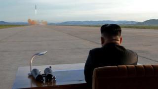 O líder da Coreia do Norte Kim Jong-un, de costas, observa o lançamento de um míssel