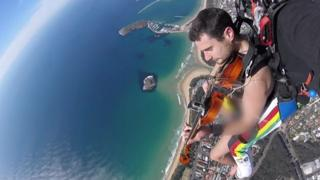 Glen Donnelly plays violin during naked skydive