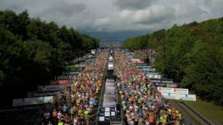Thousands of runners make their way across the start line and first few hundred metres
