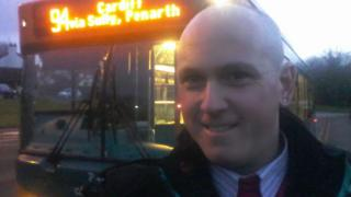 A selfie of Matthew Enos in front of a Cardiff Bus
