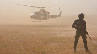 Securtiy officer stand near Nigeria Airforce plane