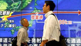 "Passersby walk in front of a TV screen reporting news about North Korea""s missile launch, in Tokyo, Japan, September 15, 2017."