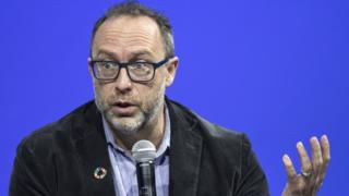 Jimmy Wales gestures with a microphone in his hand, set against a rich blue background