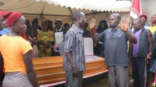 Family members near di coffin