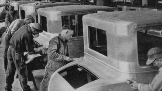 Funcionários da linha de produção dentro de uma Fábrica de Motores da Ford