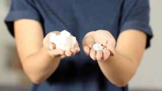 Mujer con azúcar en una mano y un edulcorante no azucarado en la otra.