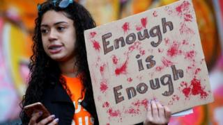 A student stands outside her New York City high school on Friday