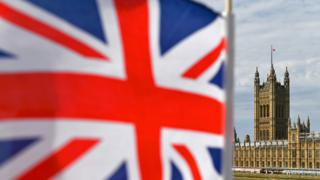 Houses of Parliament is seen from Westminster Bridge with a Union Flag in the foreground