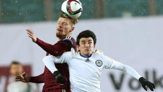 российский и казахстанский футболисты в борьбе за мяч