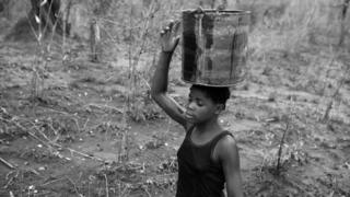 Josefina carries water home from the Rio Naranja in a bucket.