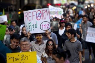 นักเคลื่อนไหวถือป้ายเรียกร้องให้ปฏิรูปกฎหมายอาญามาตรา 112 ของไทยในการเดินขบวนต่อต้านกฎหมายนี้ในกรุงเทพฯ เมื่อวันที่ 10 ธ.ค. 2554