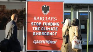 People walk past a Greenpeace protest at a Barclays branch