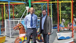 Graeme Watson and Geoffrey Boot MHK in front of the Silverdale Glen carousel