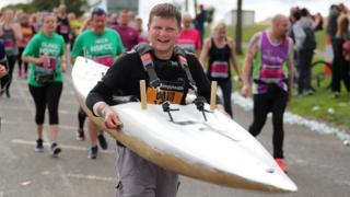 A runner carries a canoe