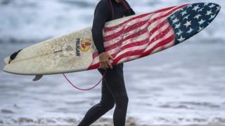 A surfer carries his patriotic board out of the water after surfing just south of the Newport Beach Pier in Newport Beach early Friday morning, September 7, 2018,