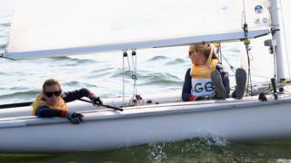 Hannah Mills and Saskia Clark wait to compete as light wind delays the start of the women's 470 race