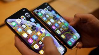 Un cliente compara un iPhone XS y un iPhone XS Max en una tienda Apple en Singapur, septiembre de 2018.