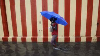 An Indian girl walks under an umbrella along a waterlogged street following heavy rain in Chennai on November 13, 2015.
