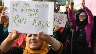 Protesters hold signs during a protest against the rape and murder of an eight-year-old child in Kashmir.