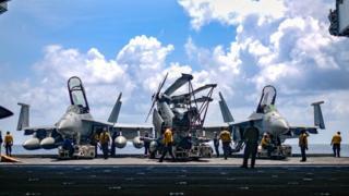Thủy thủ Hải quân Hoa Kỳ di chuyển máy bay từ thang máy vào khoang chứa máy bay của tàu sân bay USS Theodore Roosevelt ở Biển Đông hôm 8/4.