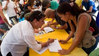 People participate during an event organized by the Venezuelan opposition collecting signatures as part of the process to seek a referendum to remove the president of Venezuela Nicolas Maduro in Caracas, Venezuela, on 27 April 2016.