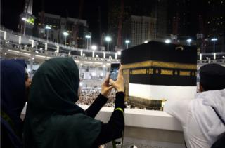 Muslim pilgrims take picture near the Islam's holiest shrine, the Kaaba, at the Grand Mosque in the Saudi holy city of Mecca, late on September 20, 2015. The annual hajj pilgrimage begins on September 22, and more than a million faithful have already flocked to Saudi Arabia in preparation for what will for many be the highlight of their spiritual lives.
