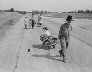 Family walking on highway - five children. Started from Idabel, Oklahoma, bound for Krebs, Oklahoma, June 1938