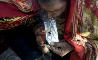Idian drug user covers himself with a blanket as he smokes smack, heroin, in old Delhi