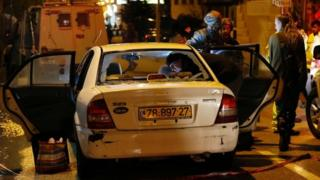 Israeli security forces inspect a damaged car outside a grocery store following the stabbing attack in the Jewish Beit Horon settlement in the West Bank (25 January 2016)