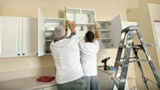 builders fitting kitchen cupboards